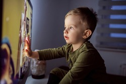 Children's addiction to television and cartoons. A boy touches the TV screen with one hand. Close up of a kid sitting right in front of the TV in his pajamas and staring at a cartoon. Modern parenting