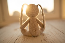 Children's animal stuffed toy bunny  sitting on wooden floor in front of the window.