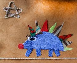 children's applique hedgehog on a paper background, applique of fabric, children's creativity,children's drawings