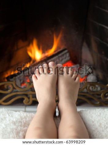 Children's bare feet are heated in the fire in the fireplace with a brass openwork lattice