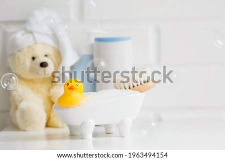 Children's bath accessories. Baby care. Bear with a towel on his head, a brush and bottles of shampoo. A miniature bubble bath and a yellow rubber duckling for bathing. Stock photo ©
