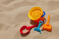 Children's beach toys - buckets, spade and shovel on sand on a sunny day