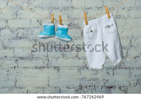Children's boots and pantyhose dry on a rope against a white brick wall. #767262469