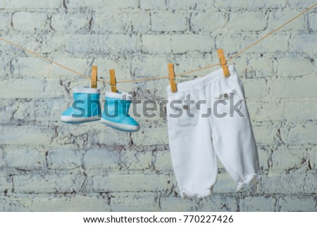 Children's boots and pantyhose dry on a rope against a white brick wall. #770227426