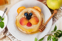 Children's breakfast pancakes smiling face of the sun lion strawberry blueberry and apricot, cute food, honey, creative idea