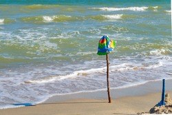 Children's cap hanging on a stick inserted on the beach, on the sea