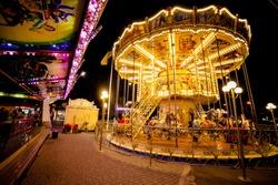 Children's Carousel at an amusement park in the evening and night illumination. amusement park at night. amusement park, picture for the background.