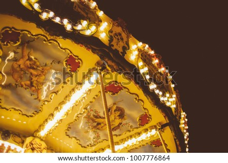 Children's Carousel at an amusement park in the evening and night illumination. amusement park at night. Outdoor vintage colorful carousel in the the city / carousel detail. Vintage photo processing