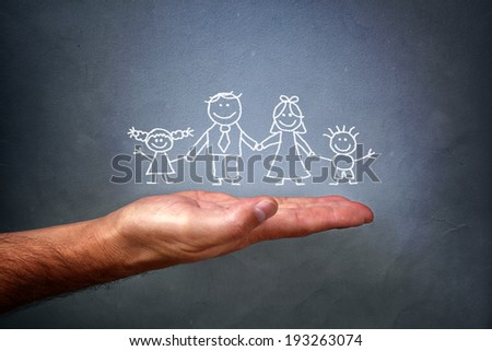 Children\'s chalk drawing on a blackboard of a happy family with mom, dad, son and daughter holding hands being held in the palm of a mans hand