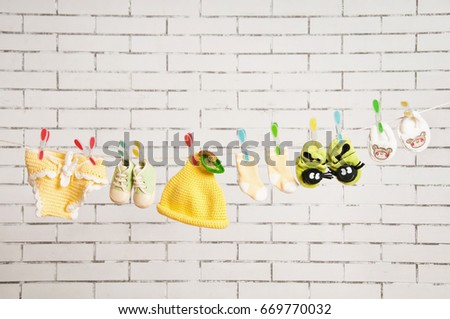 Children's clothes hanging on a rope against a white brick wall #669770032