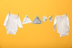 Children's clothes on laundry line against color background