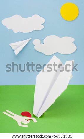 Children's collage from a paper a rough surface. The pilot lies on a  paper green grass. Wreck of the plane  concept
