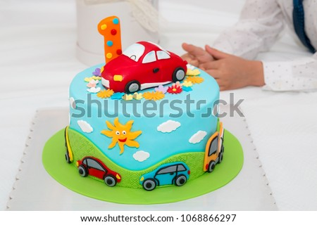 Children's colorful fondant birthday cake decorated with little cars and number one on the top.