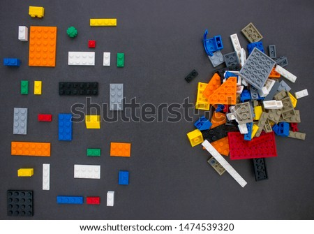 Children's constructors on black. Multi-colored cubes. Games for motor developing memory and mind. The concept of chaos and order.