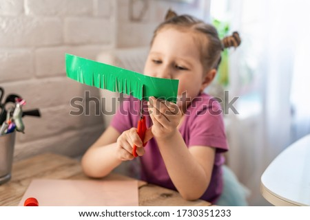 Children's creativity. A little girl enthusiastically cuts colored cardboard with scissors, cutting small strips in the form of grass on it. Skill to cut with scissors, learning new things.