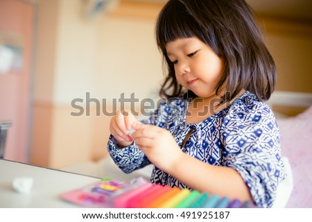 children\'s creativity. child sculpts from clay.Cute little girl moulds from plasticine on table