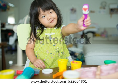 children\'s creativity. child sculpts from clay.Cute little girl moulds from plasticine on table.Dentist Concept.
