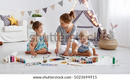 children\'s creativity. mother and children draw paints in the playroom