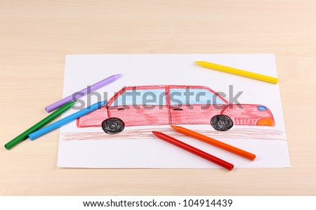 Children's drawing of red car and pencils on wooden background