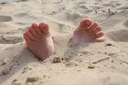 Children's feet are buried in sand