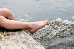 Children's feet close up splashing in the water.Summer concept. Happy childhood concept.Copy space for text