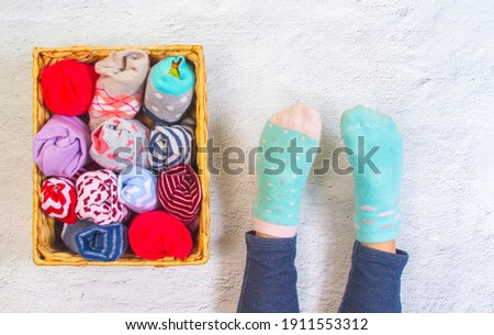 Children's feet in different blue socks and next to it a wicker basket with socks twisted into one another.