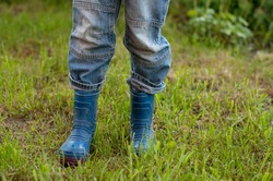 children's feet in dirty blue rubber boots and jeans stand on the grass