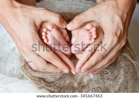 Children's feet in hands of mother and father.  Mother, father and Child. Happy Family concept. Beautiful conceptual image of Motherhood