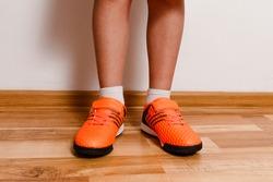 children's feet in orange sneakers indoors close