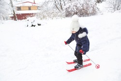 Children's feet in red plastic skis with sticks go through the snow from a slide-a winter sport, family entertainment in the open air. A little girl glides down the slope from an early age. Copy space