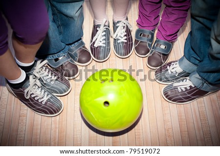 children's feet in shoes and a bowling ball for the game