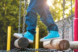 Children's feet in sneakers and jeans at the playground with swinging bridge