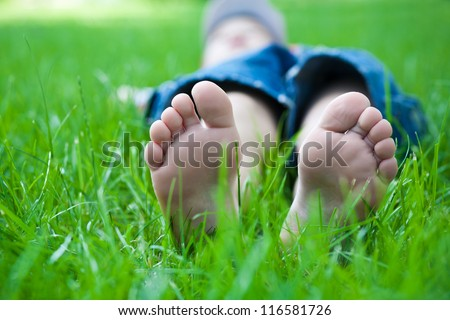 Children's feet  on grass. Family picnic in spring park