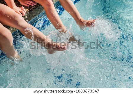 Children's feet splashing in sparkling blue pool water. Fun summertime outdoor activity of swimming and enjoying the water.