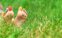 Children's feet with a pattern of paints smile on the green grass. Selective focus. nature.