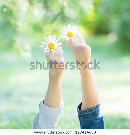 Children`s feet with flowers against green spring background. Healthy lifestyles concept