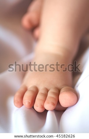Children's foot on a soft light towel