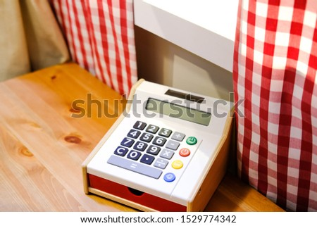 Children's games. Children's rest. A toy cash register stands on a table next to a windowsill, with two sides covered in red and white checkered curtains. Children's training, education. Maths.