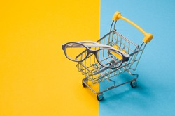 children's glasses for small children in a gray plastic frame in a small shopping cart on a colorful background, copy space, special anti-vandal frame for children's glasses