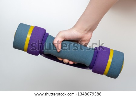 children's hand hold a dumbbell. the dumbbell is covered with soft fabric. White background