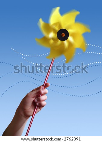 Children's hand holding a yellow toy windmill.