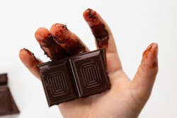 Children's hand holding melted chocolate
