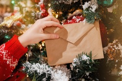 Children's hand holds an envelope with a letter to Santa on Christmas Eve against the background of a decorated Christmas tree with bright lights. Selective focus.