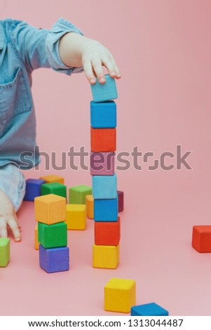 Children's hand is building a tower of wooden colored cubes. #1313044487
