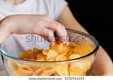 children's hand takes chips out of glass bowls, harmful food. #1030966264