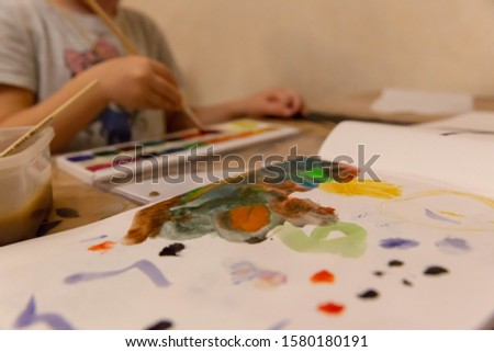 Children's hand with a brush with a wooden handle draws on a white sheet of paper album for drawing, lying on the table, colorful watercolor paints in children's art school.