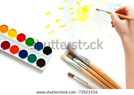 Children's hand with paint and brush