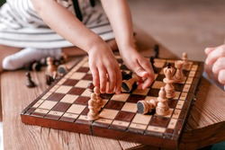 children's hands collect chess. Board game, wooden chess