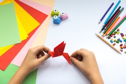 Children's hands do origami  bird from red paper. Working place is decorated with leaves of color paper, scissors, colored wood ladybugs and pencils.