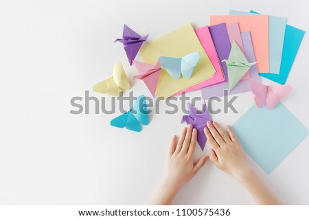Children's hands do origami from colored paper on white background. lesson of origami
